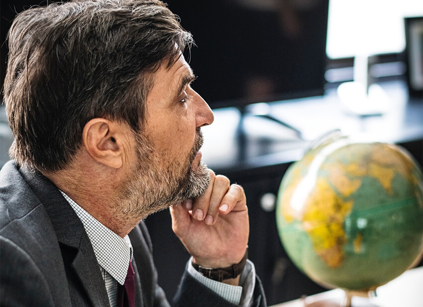 Man thinking with globe in background