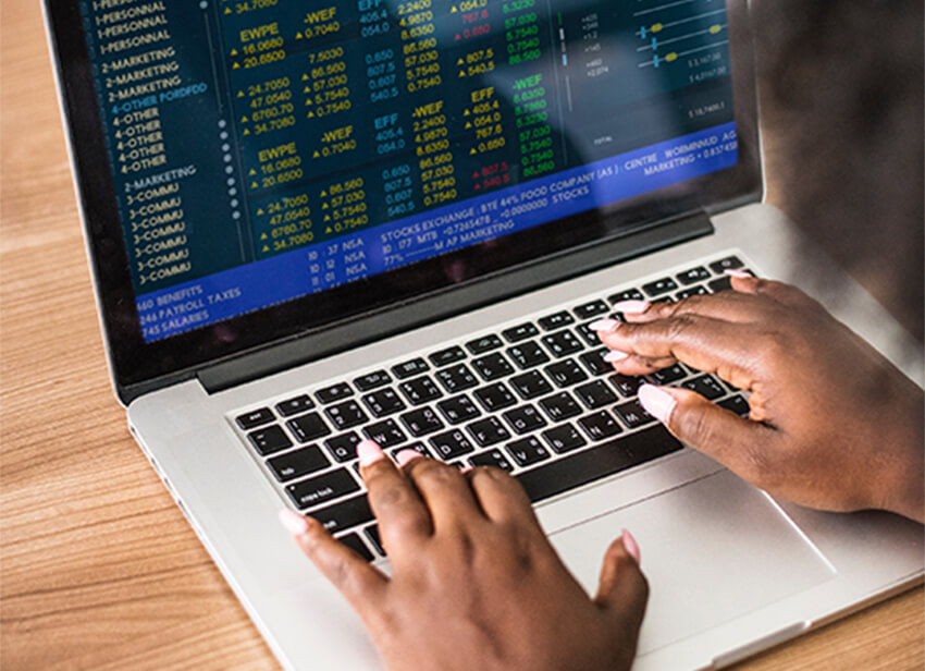 hands typing on computer with financial data on the screen